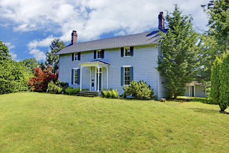 two story: Two story house with blue exterior paint and small open porch. View of grassy front yard with bushes.