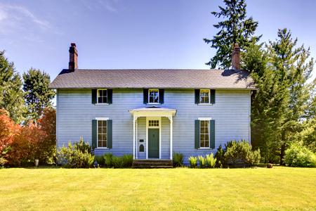 Américaine maison à deux étages avec de la peinture extérieure bleu et petit porche ouvert avec porte d'entrée verte.