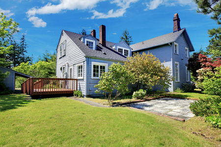 curb appeal: Classic house with curb appeal. View of wooden walkout deck and grassy filled garden with trees. Stock Photo