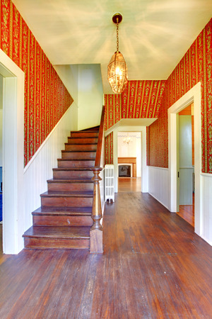 Image of Hallway with wooden staircase, red pattern wallpaper and white siding wall trim.
