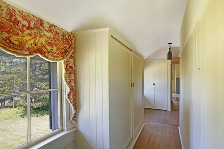 Bright empty hallway with white closets, hardwood floor and vaulted ceiling.