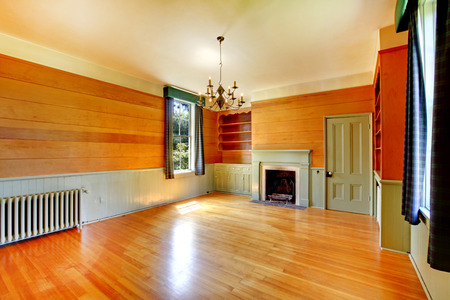 unfurnished: Bright empty wooden living room interior with fireplace, glossy hardwood floor and built-in cabinets. Stock Photo