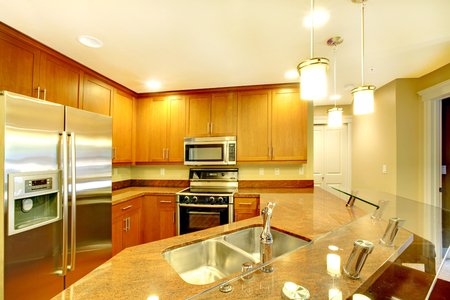 kitchen counter top: Bright kitchen room interior with granite counter top, breakfast bar and stainless steel appliances.