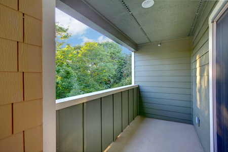 Unfurnished covered balcony with blue walls, white trim and a view.
