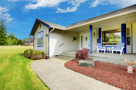 trim: Curb appeal of beige house with blue trim. Cozy entrance porch with chairs and view of concrete walkway.