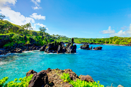 beach landscape: Waves breaking on the rocks on a sunny day during a spectacular ocean view on the Road to Hana, Maui, Hawaii, USA