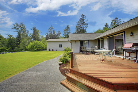 deck: View of wooden walkout deck with patio area. Backyard garden with concrete walkway and green lawn.
