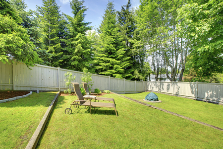lawn area: Green backyard area with well kept lawn, wooden fence and nice view.  Stock Photo