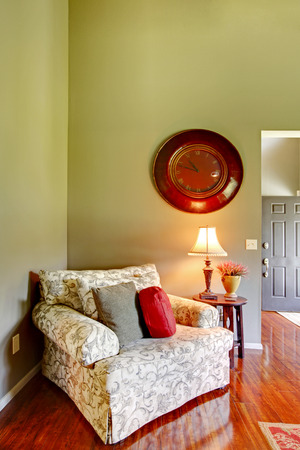 living room wall: Comfortable armchair with pillows in the corner of the living room. Antique Wall Clock on green wall and polished hardwood floor in the room.