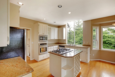 kitchen counter top: White new small simple classic American kitchen interior with kitchen island, granite counter top and hardwood floor. Stock Photo