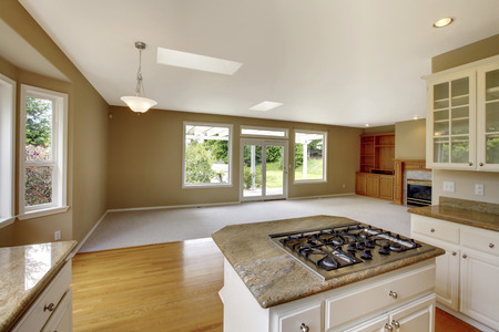 open floor plan: Empty house interior with open floor plan. Living room with fireplace and grey walls. View of kitchen area