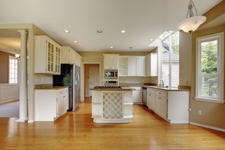 kitchen cabinets: Small classic American kitchen interior with white cabinets and kitchen island. Shiny hardwood floor.