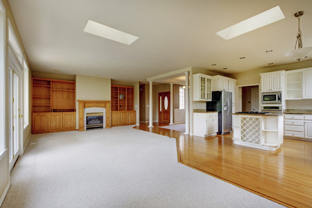 fireplace living room: Empty living room with fireplace and connected kitchen, hardwood floor Stock Photo