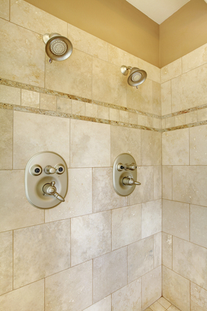 walk in: Modern new walk in shower with beige tiles and two heads.