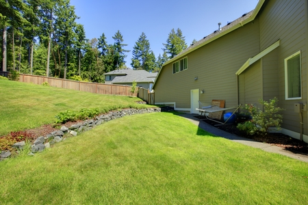lawn area: Spacious fenced backyard area with Natural Stone Landscaping and well kept lawn Stock Photo