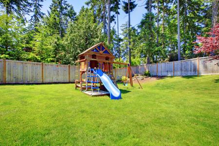superficie: Juega a los niños zona de suelo con rampa en el patio trasero cercado. Exterior de la casa. Foto de archivo