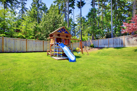 fenced in: Play kids ground area with chute in fenced backyard. House exterior.