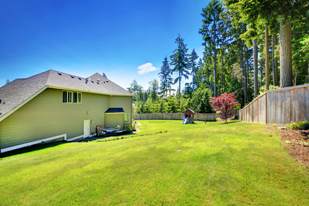home and garden: Spacious fenced backyard area with play set for kids on green lawn.