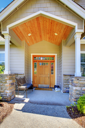 front porch: Nice entrance porch of a luxury beige house with columns, bench and wooden front door.