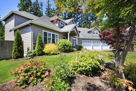 Schöne Kandareanklang des klassischen amerikanischen Haus mit schönen Landschaftsgestaltung der Vorgarten.