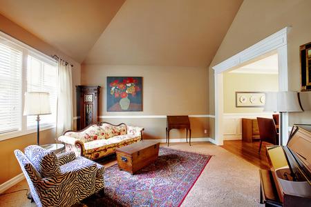 高いアーチ型天井とピアノと明るい茶色のトーンで居心地の良いリビング ルーム。旧式なグランドファーザー時計、胸および東洋の敷物と内装です。 写真素材 - 59944976