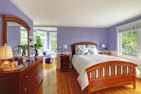 hardwood floor: Adorable bright bedroom interior with purple walls, brown furniture and hardwood floor.
