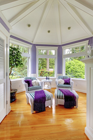 the vaulted: Vaulted ceiling living room in purple tones with two stripped armchairs and hardwood fllor. Stock Photo