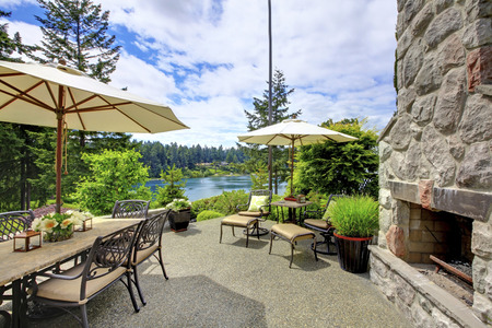 table and chairs: Patio area with stone fireplace, concrete floor, patio table set and deck chairs.