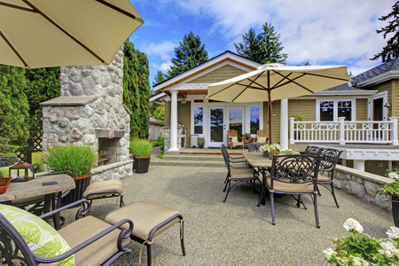 stone fireplace: Patio area with stone fireplace and concrete floor. Patio table set with umbrella and deck chairs.