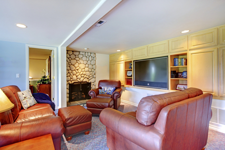stone fireplace: Classic living room interior with stone fireplace and dark brown leather sofas.