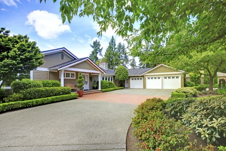 curb: Green house with beautiful curb appeal. View of three car garage and driveway