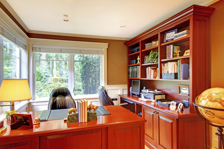 home office interior: Home office luxury interior with grey walls and wood. Furnished with wooden desk and leather chairs.