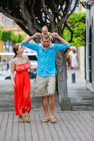 walking baby: A family of three are walking. Baby girl is sitting on her fathers shoulders. They all look happy