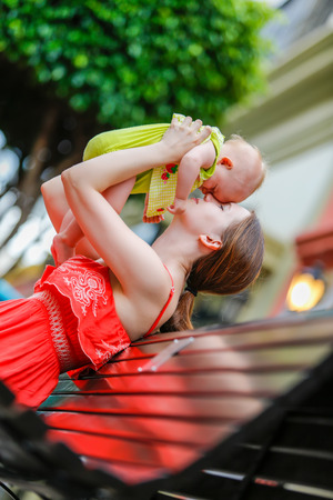 mother on bench: Happy mother in red dress sitting on a wooden bench and throws baby daughter up outdoors Stock Photo
