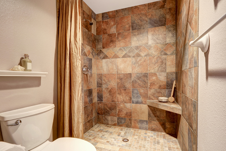 glass doors: Shower with beige title and toilet in the bathroom
