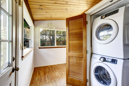 Laundry room with hardwood floor and view to fenced back yard