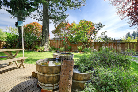 back yard pond: Fenced back yard with patio area and beautifully designed pond with waterfall. Stock Photo