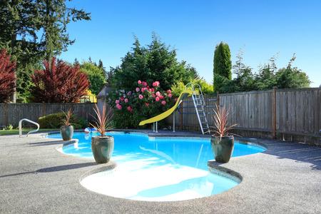 Omheinde achtertuin met een klein mooi zwembad en speeltuin Stockfoto