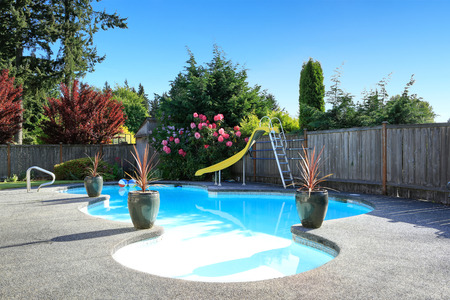 Fenced backyard with small beautiful swimming pool and playground Foto de archivo