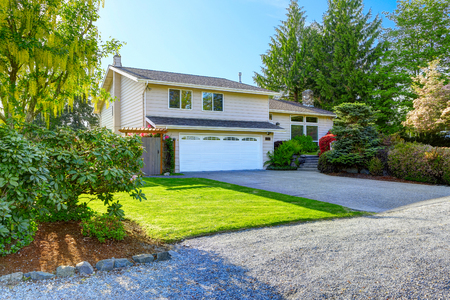 curb appeal: American house with beautiful curb appeal. View of car garage and driveway