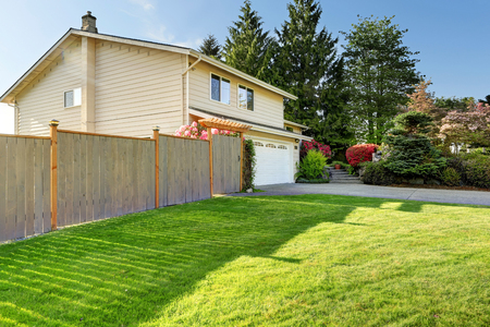 curb appeal: American house with beautiful curb appeal. View of car garage, wooden fence and driveway