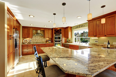 kitchen counter top: Luxury kitchen with tile floor, stained cabinets and granite counter top