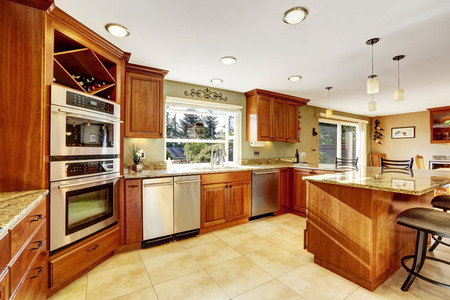 tile floor: Luxury kitchen with tile floor, stained cabinets and granite counter top