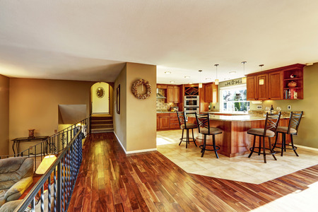 granite kitchen: Luxury kitchen connected to living room. Kitchen with tile floor, stained cabinets and granite counter top