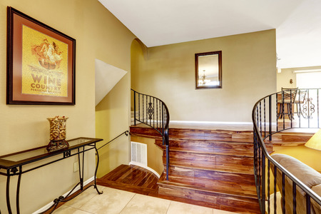 entertaining area: Large bright hallway interior design. Nice basement staircase with metal railing and hardwood floor.