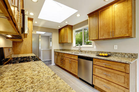brown granite: Modern kitchen room with matte brown cabinets, shiny granite tops, steel stove with hood Stock Photo