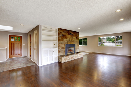 contemporary house: Large empty living room with fireplace and hardwood floor.