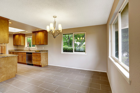 matte: Modern kitchen room with matte brown cabinets, shiny granite tops, steel stove with hood and tile floor