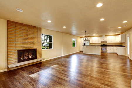 fireplace living room: Large empty living room with fireplace and hardwood floor. Living room connected to kitchen Stock Photo