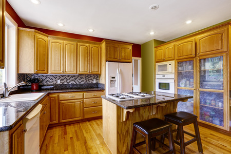 kitchen island: Small kitchen with island, dark granite counter top, also red walls and hardwood floor